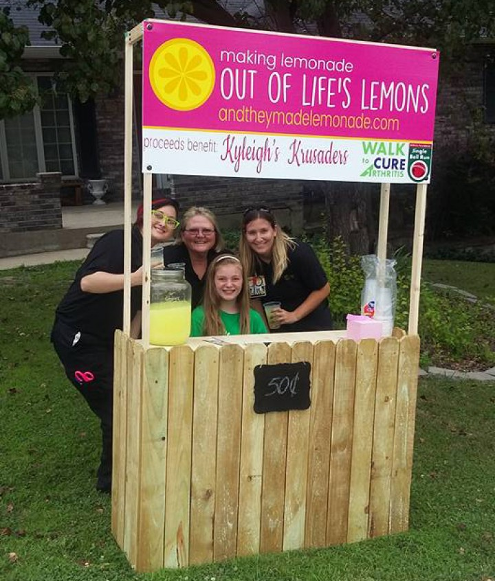 Kyleigh O'Brien poses with MU Health Care employees at her lemonade stand.