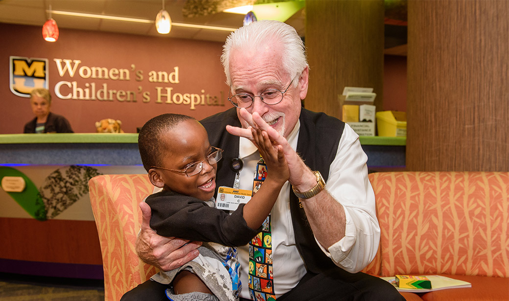 Photo of Dave Covert with patient at MU Women's and Children's Hospital.