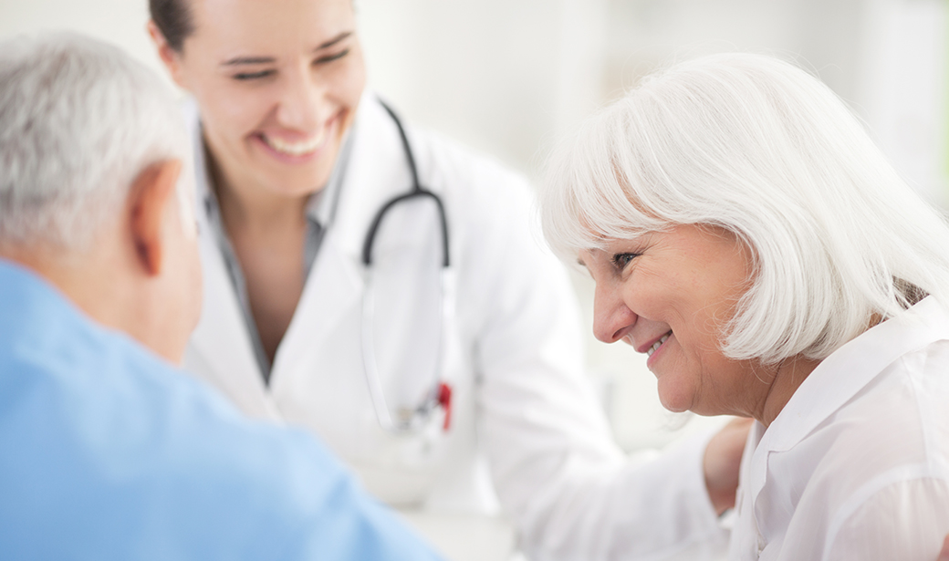 doctor smiling and helping elderly patient