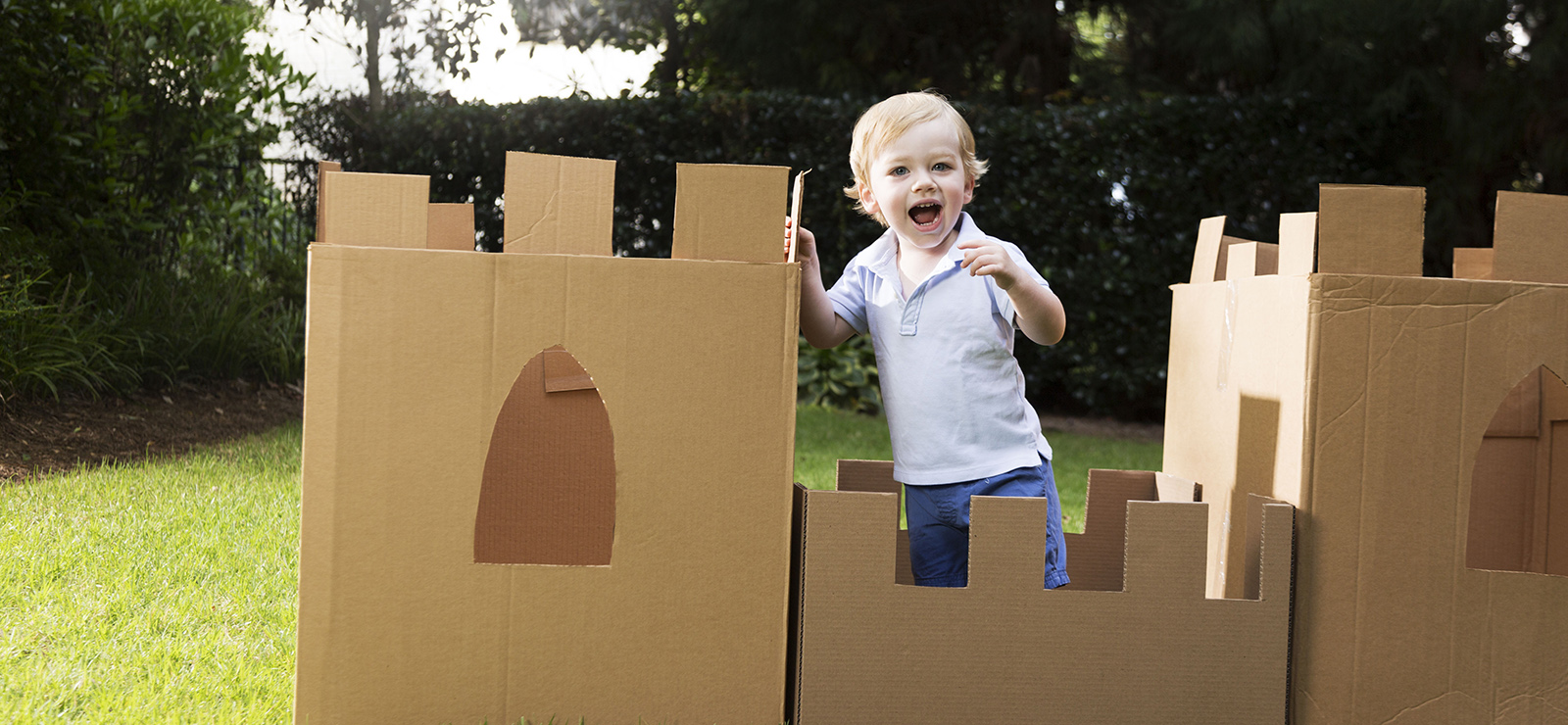 young boy plays in the yard with a castle made from cardboard box
