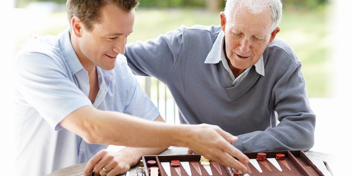 Adult grandson playing a board game with his grandfather who has Parkinson's disease