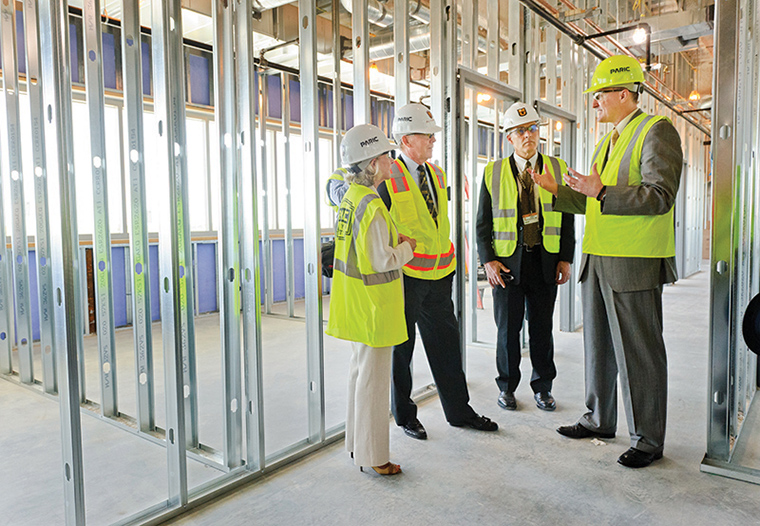 James Cook, DVM, PhD, explains plans while on a tour of the construction site for the Thompson Laboratory for Regenerative Orthopaedics at the Missouri Orthopaedic Institute. From left: Nancy Thompson, Bill Thompson, James Stannard, MD, and Cook.