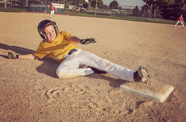 Photo of young baseball player sliding into second base.