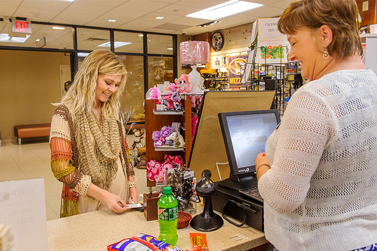 Photo of someone in gift shop buying snacks.