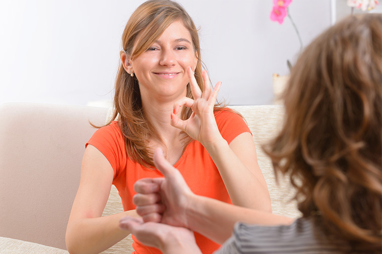 Photo of two women using sign language.