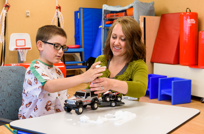 Boy building cars with woman in rehab