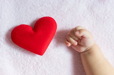 Baby hand reaching for stuffed heart toy