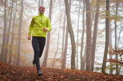 Photo of man running on wooded trail