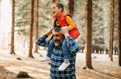 Photo of Grandpa holding grandson on his shoulders