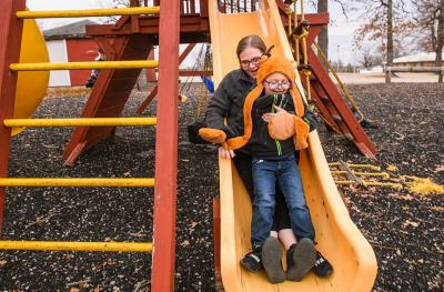 Carol Sparks-McCord goes down a slide with her son Nicholas at a park near their home in Dixon, Missouri.