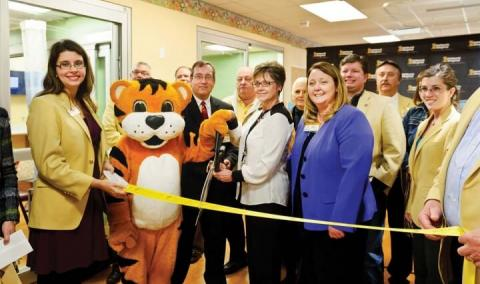 T.J., the MU Children's Hospital mascot, helps cut the ribbon at an open house for the hospital's renovated Neonatal Intensive Care Unit on Dec. 8, 2014. From left: Michelle Kemp, Columbia Chamber of Commerce ambassador; T.J.; John Pardalos, MD, medical director of the NICU; Judy Bildner, RN, nurse manager; and Keri Simon, executive director of MU's Women's and Children's Hospitalc