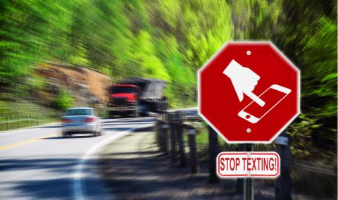 Stop sign with a symbol of a handheld device and the words Stop Texting printed on it. Image is blurred to imply motion and distraction. Symbol is artist own conceptual design.