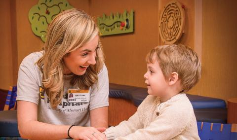 Brittany Riley, a certified Child Life specialist, plays with 3-year-old Leo Lynch at MU Health Care's Children's Hospital.