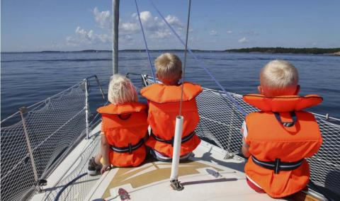 Three children sitting in the front of a sailboat wearing life jackets.