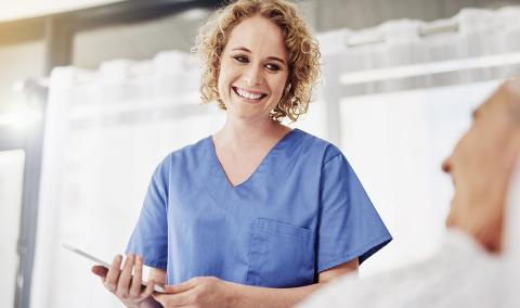 smilng female doctor holding a tablet with patient