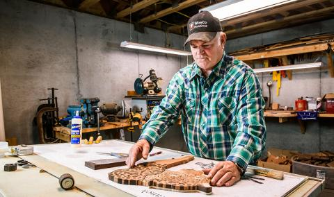Rick Allain builds a jaguar from pieces of wood in his basement workshop