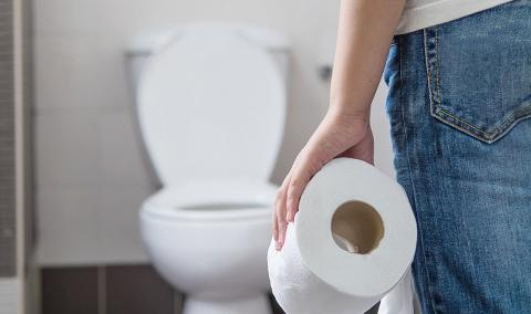 person at toilet with toilet paper
