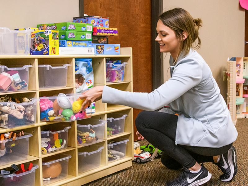 Employee organizes toys on shelf