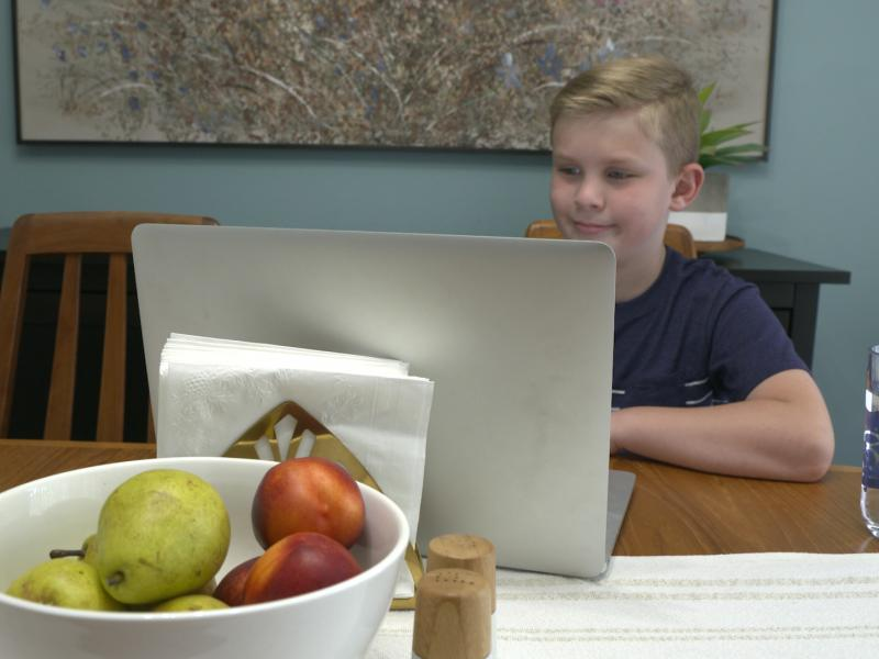 Boy works on laptop at kitchen table