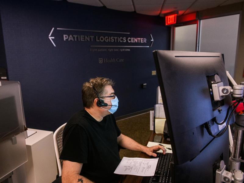 Man looks at computer monitor in Patient Logistics Center