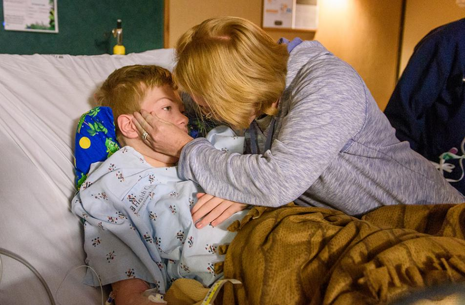 boy in hospital bed hugged by mother
