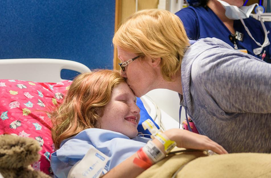 child in hospital bed kissed by mother