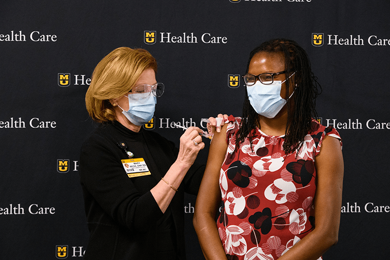 Chief Nursing Officer Mary Beck, DNP, RN, vaccinates pediatric infectious disease specialist Christelle Ilboudo, MD