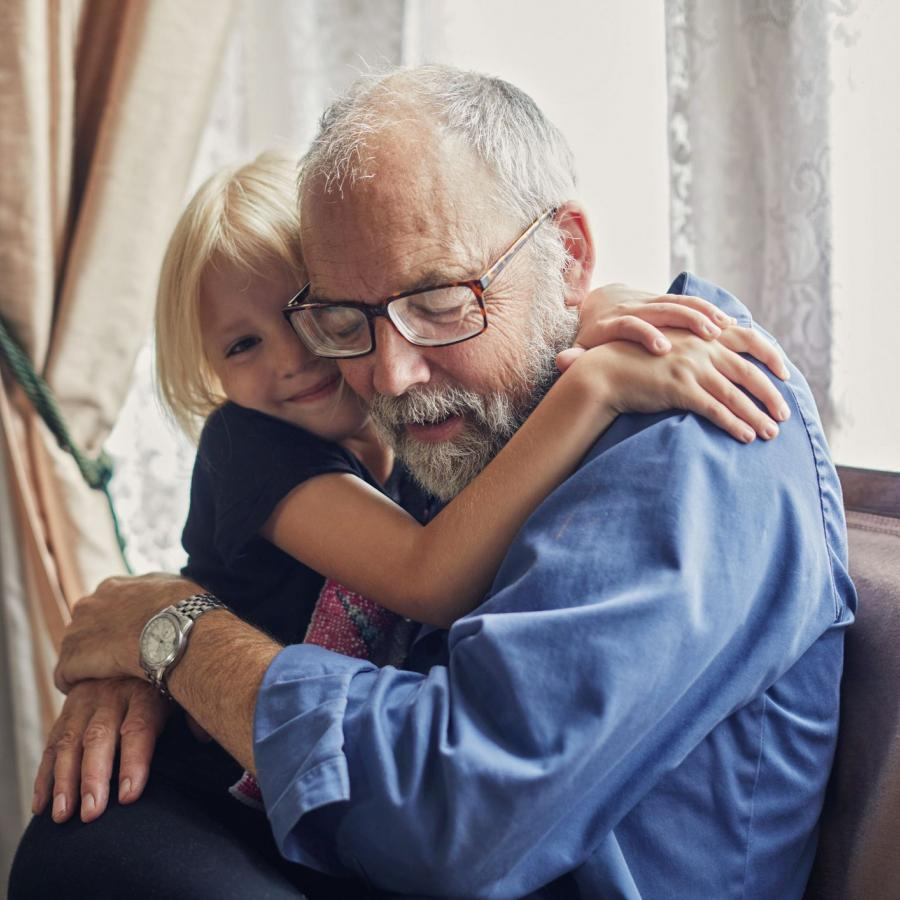 little girl hugging old man