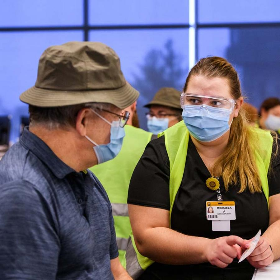Photo of vaccinator talking to man